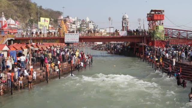 thousands of devotees bathing at the sacred ghats of ganges / haridwar is an ancient city and important hindu pilgrimage site where the river ganges... - foothills stock videos & royalty-free footage
