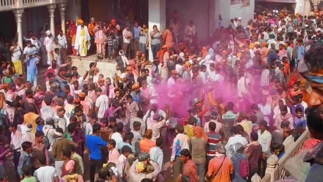 vídeos y material grabado en eventos de stock de thousands of devotees dancing / religious festivities and celebrations inside the temple complex in nandgaon mathura the village of lord krishna holi... - krishna