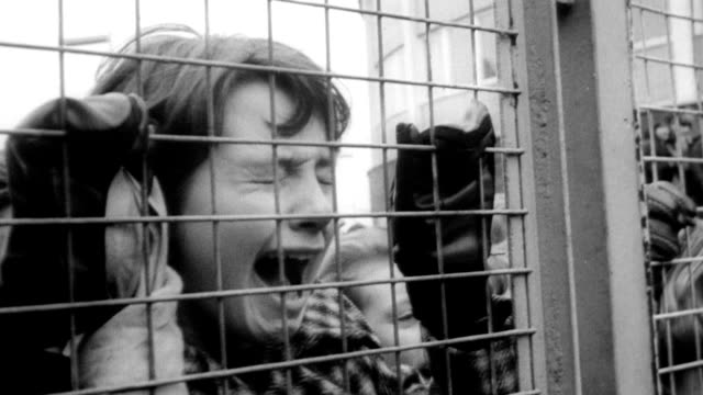 vídeos de stock, filmes e b-roll de thousands of fans screaming for the beatles upon their return to london / hysterical girls pushing themselves against fence / police holding fences... - 1964