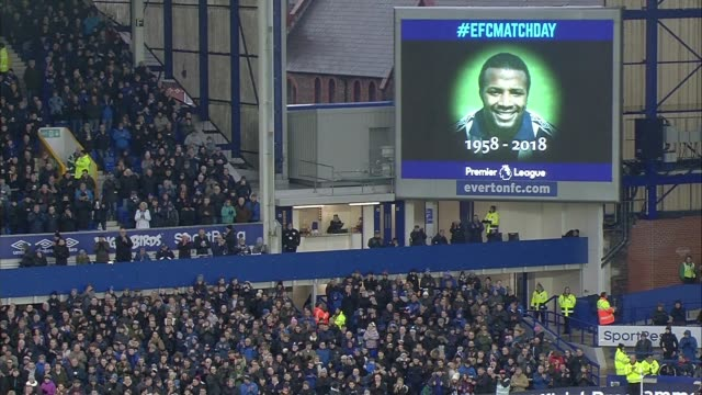 thousands of football fans honour cyrille regis; england: merseyside: liverpool: goodison park: ext everton v west bromwich albion: various of fans... - itv weekend late news点の映像素材/bロール