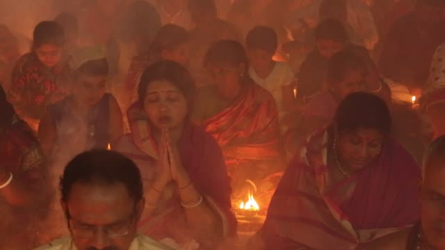 thousands of hindu devotees sit with prodip and pray to god in front of shri shri lokanath brahmachari ashram temple during the religious festival... - traditional ceremony stock videos & royalty-free footage