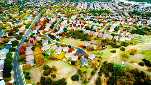 thousands of houses within fall foliage autumn suburb neighborhood aeiral drone view high above expanding housing development - modern rock stock videos & royalty-free footage