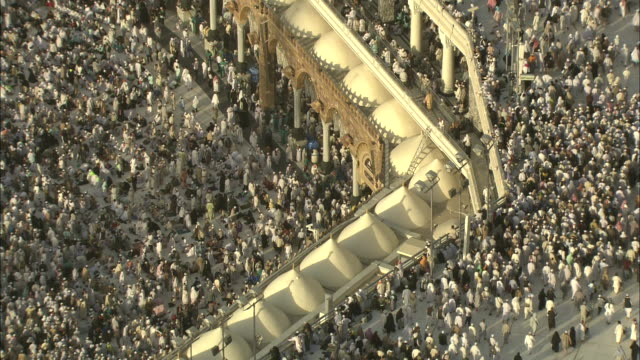 Thousands of Islamic pilgrims surge around the sacred site at Mecca.