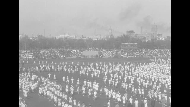 thousands of japanese schoolchildren run onto field and perform calisthenics; girls dance and hop in place; five trumpeters / a band plays on... - haarzopf stock-videos und b-roll-filmmaterial