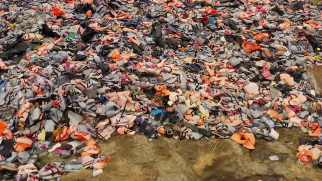 thousands of life jackets and rubber boats abandoned by migrants who have made the crossing from turkey to the greek island of lesbos are dumped on... - flytväst bildbanksvideor och videomaterial från bakom kulisserna