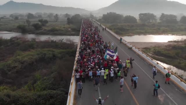 thousands of migrants crossing mexico toward the united states in a caravan are temporarily stopped on the highway between arriaga and san pedro... - finishing stock videos & royalty-free footage