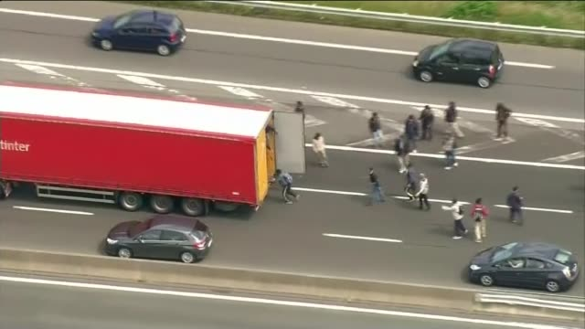 thousands of migrants storm eurotunnel terminal in calais lib calais view aerial of migrants running after moving lorry and one jumping on - calais stock videos and b-roll footage