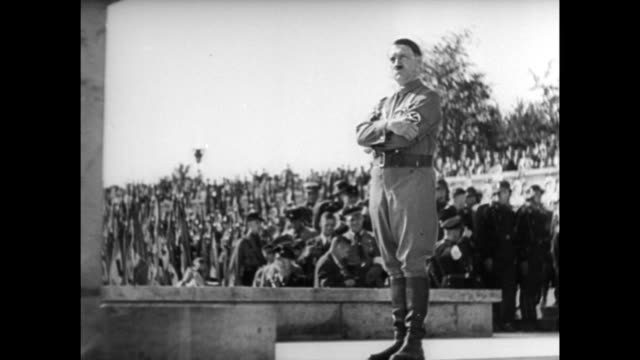 Thousands of Nazi troops attend rally / Nazi swastika banners hanging / Nazi troops with trumpets / Adolf Hitler standing with arms crossed Nazi...