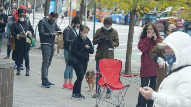 thousands of new york city citizens wearing face mask waiting in line for hours in the chilly morning for early voting on the 2020 presidential... - using phone stock videos & royalty-free footage