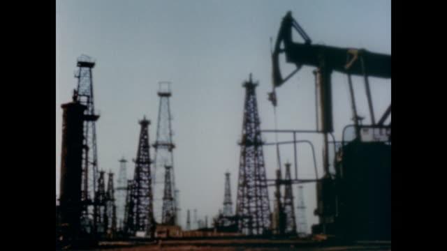 1947 thousands of oil derricks surround the city of los angeles - 石油産業点の映像素材/bロール