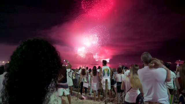thousands of people celebrate new year's eve admiring the fireworks display at copacabana beach. - firework display stock-videos und b-roll-filmmaterial