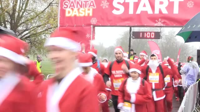 vídeos de stock, filmes e b-roll de thousands of people dressed as santa claus to make their way around 5k or 10k courses in clapham common to help raise funds for great ormond street... - festa beneficente