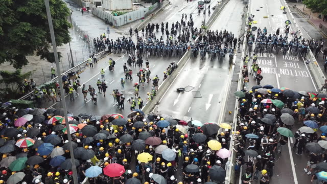 thousands of people gather to protest the handover flag raising ceremony in hong kong police clashed with protesters using nightsticks and pepper... - protestor stock videos & royalty-free footage