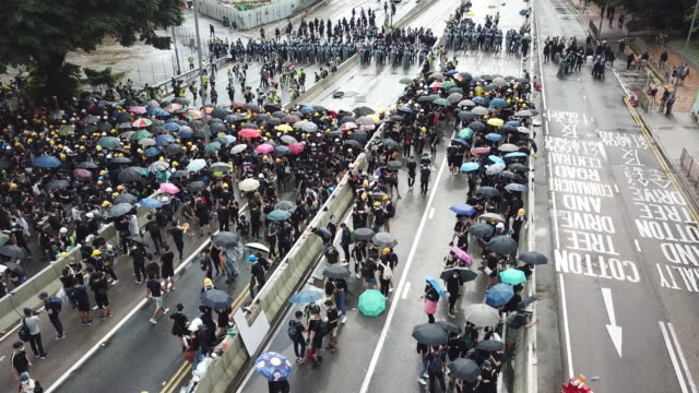 thousands of people gather to protest the handover flag raising ceremony in hong kong. police clashed with protesters using nightsticks and pepper... - hong kong flag stock videos & royalty-free footage