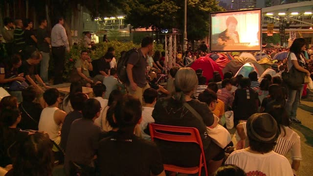 thousands of people gather to watch the live retransmission of talks between the hong kong authorities and pro democracy protest leaders after weeks... - occupy central stock videos & royalty-free footage