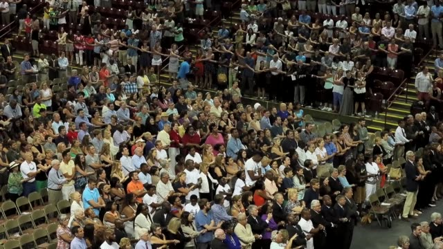 thousands of people hold hands and sing 'we shall overcome' during a prayer vigil for the nine victims of the emanuel ame church shooting at the... - congregation stock videos & royalty-free footage