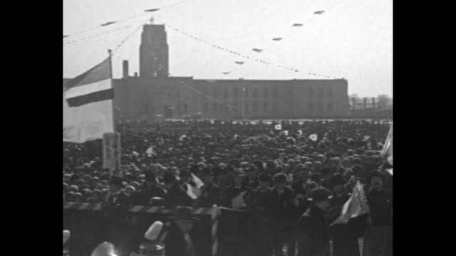 thousands of people in city square with flags waving in a stiff breeze / small boys in winter clothes and fur hats / flapping japanese and manchukuo... - mandschurei stock-videos und b-roll-filmmaterial