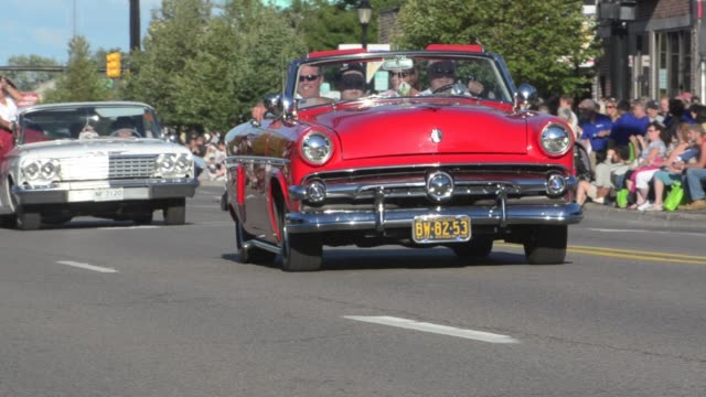 vídeos de stock, filmes e b-roll de / thousands of people line the streets to watch a parade of classic cars during the 17th annual woodward dream cruise / car parade and artist... - hot rod