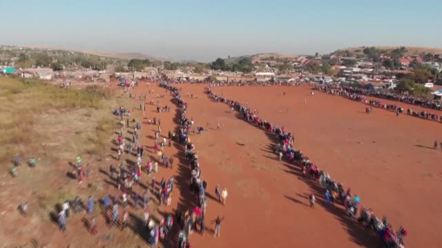stockvideo's en b-roll-footage met thousands of people queue up in the early morning in the informal settlement of iterileng pretoria to receive food hampers masks soap and hand... - hongerig
