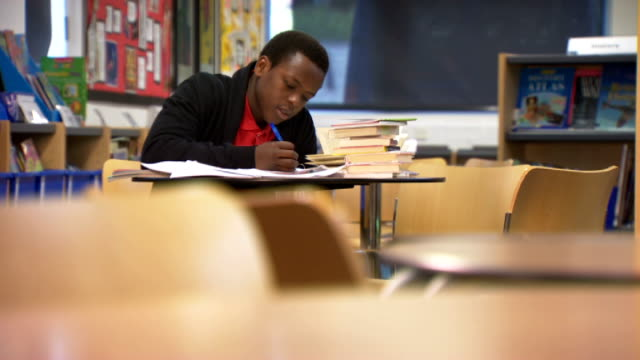 thousands of pupils forced to re-sit gcse exams; gvs jonathan clarke working at desk in library - 一般教育証明試験点の映像素材/bロール