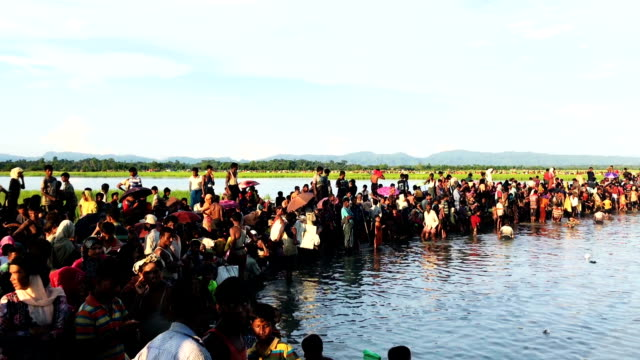 Thousands of Rohingya refugees flee from Myanmar are kept under a tight security by Bangladeshi military after crossing the border in a rice patty...
