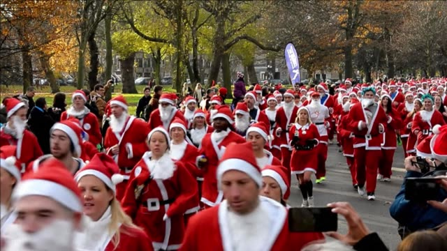 thousands of runners dressed as father christmas take part in the charity fundraising santa run in victoria park north london on sunday clean... - victoria park london stock videos & royalty-free footage
