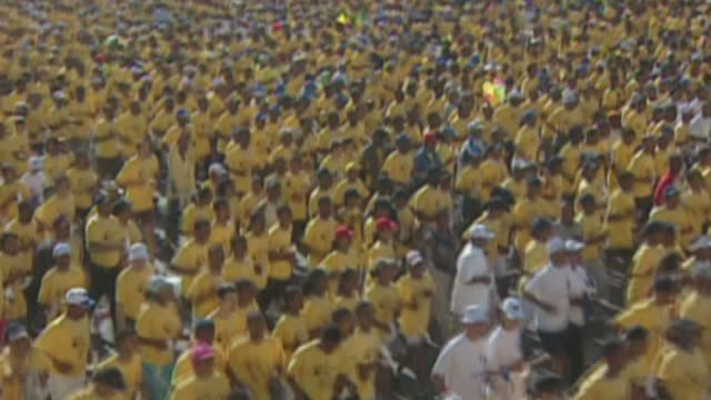 thousands of runners in race all wearing the same color shirts, yellow, - all shirts stock-videos und b-roll-filmmaterial