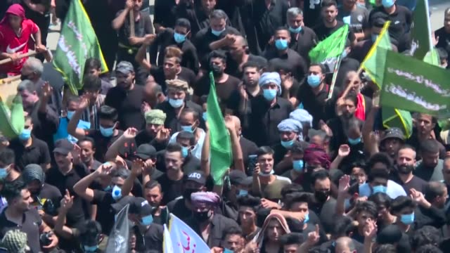 thousands of shiite muslims wearing masks flood the streets of iraq's holy city of karbala to mark ashura, in one of the largest religious gatherings... - iraq video stock e b–roll