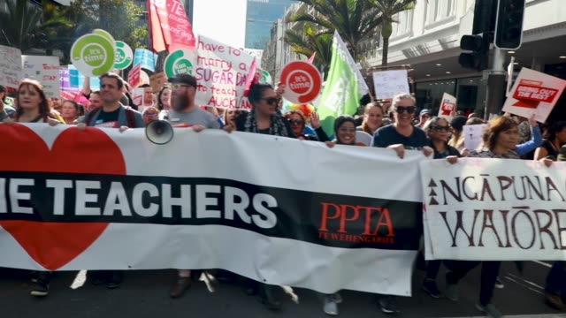 thousands of teachers parents and school children march up queen street as they protest on may 29 2019 in auckland new zealand some 50000 school... - new zealand culture stock videos and b-roll footage