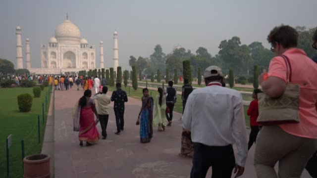 thousands of tourists stream in to visit the taj mahal the iconic 17th century marble mausoleum as hazardous smog blankets new delhi and north india - tourism stock videos & royalty-free footage