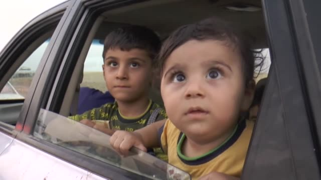 thousands of yazidi and christian people flee hamdaniyah town of mosul to erbil after the latest wave of isil advances that began on sunday has seen... - mosul stock videos and b-roll footage