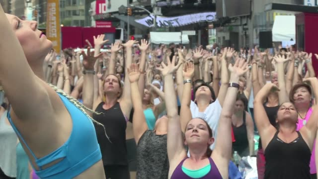 thousands of yoga aficionados celebrate the summer solstice amid the neon lights and cacophony of times square searching for inner peace in the heart... - summer solstice stock videos and b-roll footage