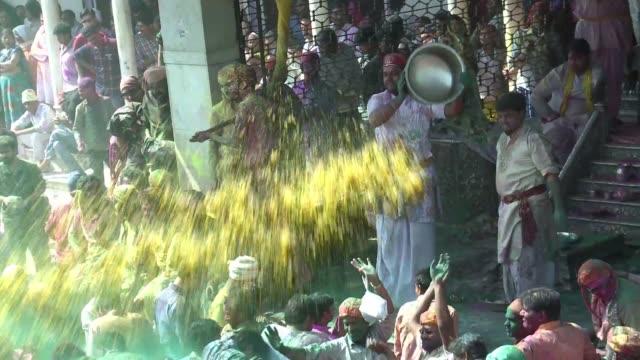 vídeos y material grabado en eventos de stock de thousands play with colour powders and women beat men with sticks in the village of hindu god krishna as part of the lathmar holi festival - krishna