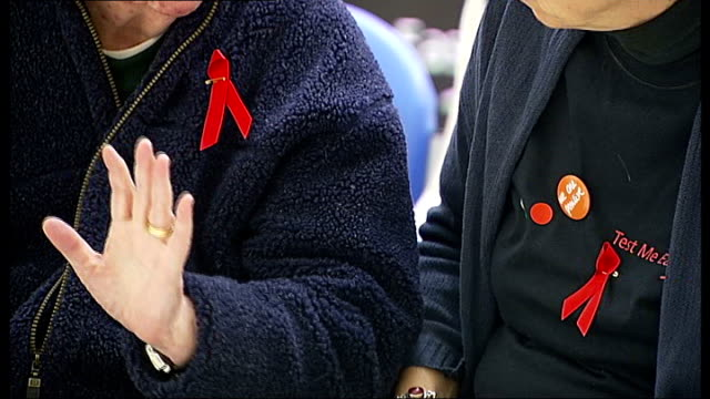 thousands unaware of hiv status / london hospital offering hiv tests to all outpatients; people wearing red ribbons 'blood tests' sign vials in blue... - retrovirus video stock e b–roll