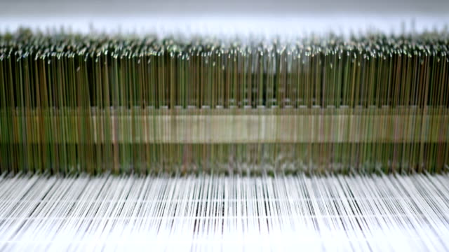 threads on a loom in  weaving loom machine in textile factory - needle plant part stock videos & royalty-free footage