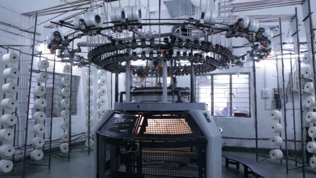 Threads stretch from a circular knitting machine at a Rajlakshmi Cotton Mills Ltd garment factory in Kolkata West Bengal India on Monday Dec 25 Close...