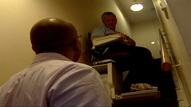 threat of demolition removed from six houses in stokeontrent walker on stairlift as along up stairs in house talking to reporter walker reaching top... - stair lift stock videos and b-roll footage