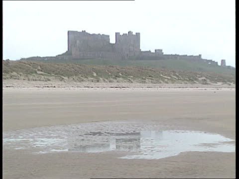 Banburgh Banburgh Castle GV Bamburgh Castle TILT UP from pool in beach GV Castle seen in distance as grass on sand dunes f/g Berwick Upon Tweed...