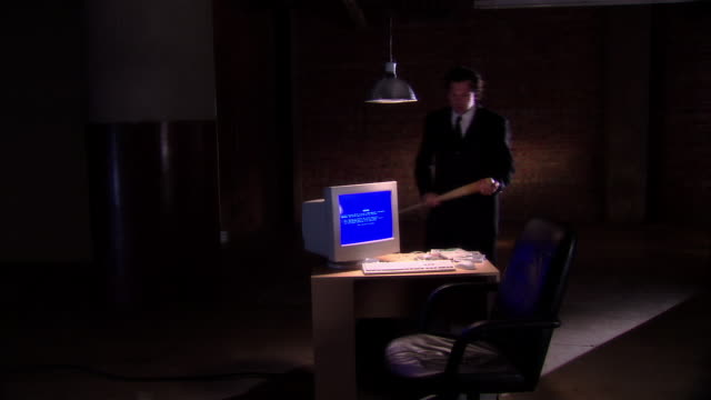 ms threatening businessman with baseball bat walking toward pc on table under overhead light in interrogation room with blue windows error message/ man beating keyboard with bat  - interrogation stock videos and b-roll footage