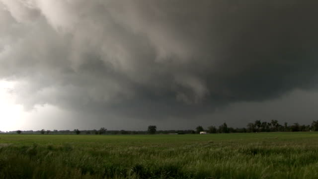 threatening storm clouds hover over a wheat field in nebraska as a supercell thunderstorm approaches - nebraska stock-videos und b-roll-filmmaterial