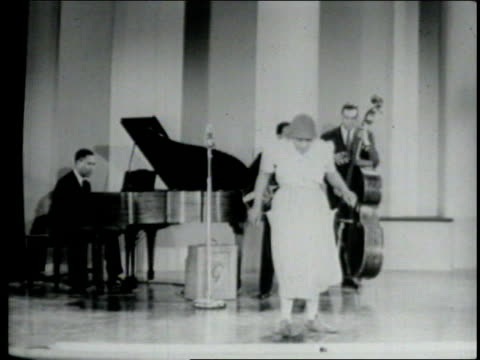 """three adult african american male musicians on stage playing double bass, acoustic guitar, and piano; jackie """"moms"""" mabley interrupts luther, the... - plucking an instrument stock videos & royalty-free footage"""