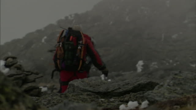 three adults backpack over rugged terrain as a storm blows around them. - survival stock videos & royalty-free footage