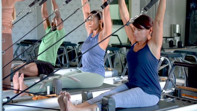 tre vuxna i pilates studio med fitness instruktör - människoarm bildbanksvideor och videomaterial från bakom kulisserna