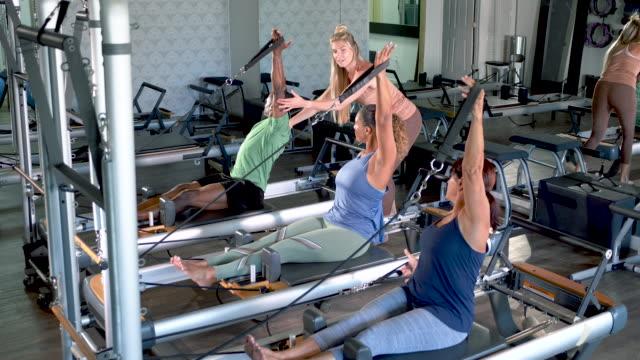 vidéos et rushes de trois adultes dans le studio de pilates avec l'instructeur de forme physique - performance athlétique