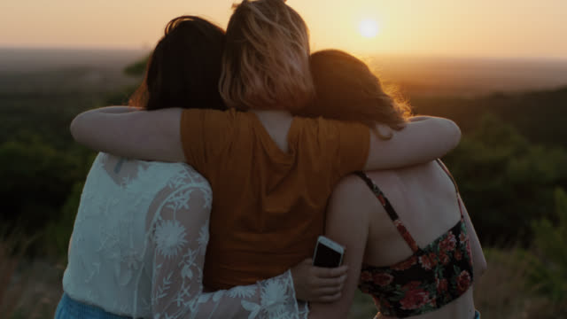 MS SLO MO. Three adventurous friends hug on green mountainside as sun sets over valley.