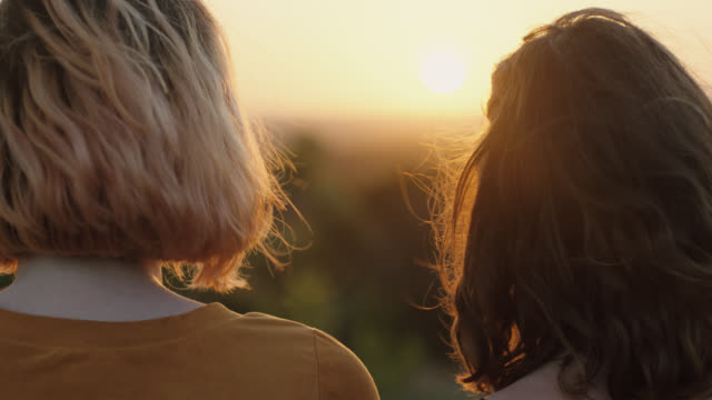 vídeos de stock e filmes b-roll de ms slo mo. three adventurous girls on mountainside look out over valley at sunset. - meninas adolescentes