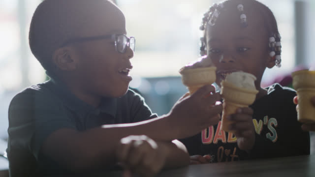 slo mo. three african-american children toast their ice cream cones at an ice cream shop - braided hair stock videos & royalty-free footage