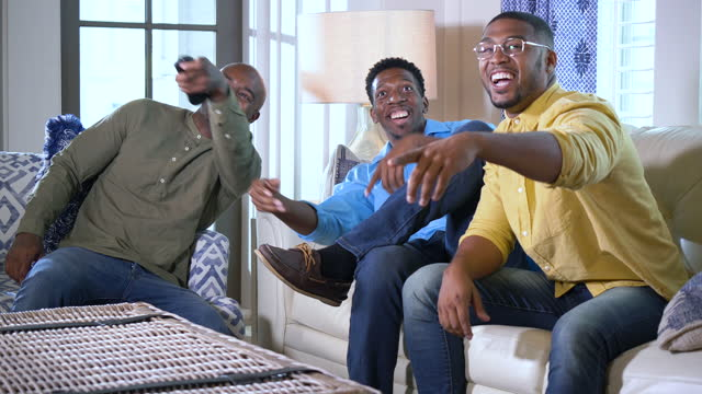 three african-american men sit down to watch tv - mid adult men stock videos & royalty-free footage