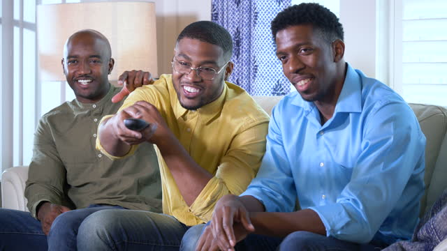 three african-american men watch tv, change channels - mid adult men stock videos & royalty-free footage