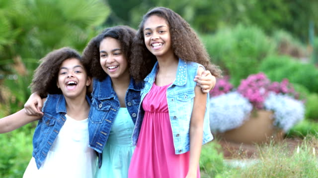 Three African-American sisters smiling in garden
